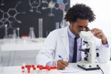 Shot of a male biologist looking at a glass slide through a microscope